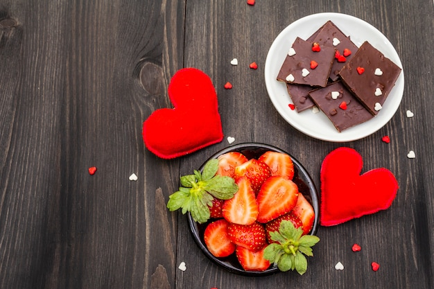 Romantyczna koncepcja walentynki. czekolada, świeża dojrzała truskawka, czerwone filcowe serca. słodki deser dla miłośników.
