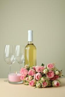 Romantyczna koncepcja z różami, winem i świecą na beżowym stole