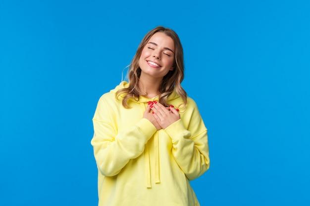 Romantyczna kusząca blond kaukaska dziewczyna w żółtej bluzie z kapturem, przyciska dłonie do serca i zamyka oczy
