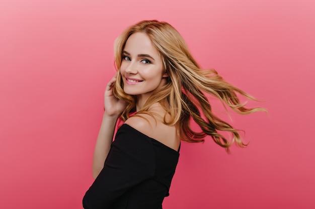 Romantyczna ładna młoda dama patrząc przez ramię, pozując na różowej ścianie. inspirowana biała dziewczyna z kręconymi blond włosami machająca.