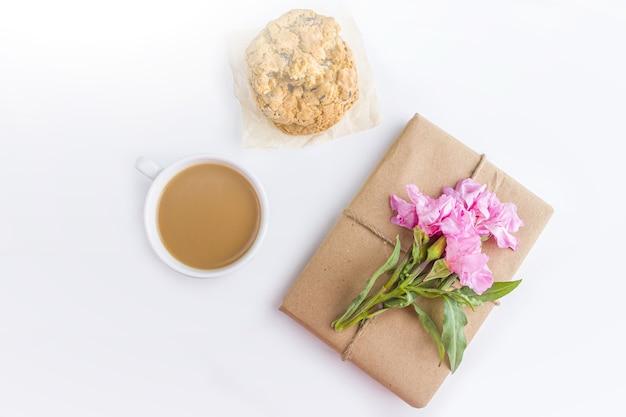 Romantyczna martwa natura w stylu vintage z ładnym pudełkiem zapakowanym w brązowy papier rzemieślniczy i ozdobionym różowym kwiatkiem na białym tle