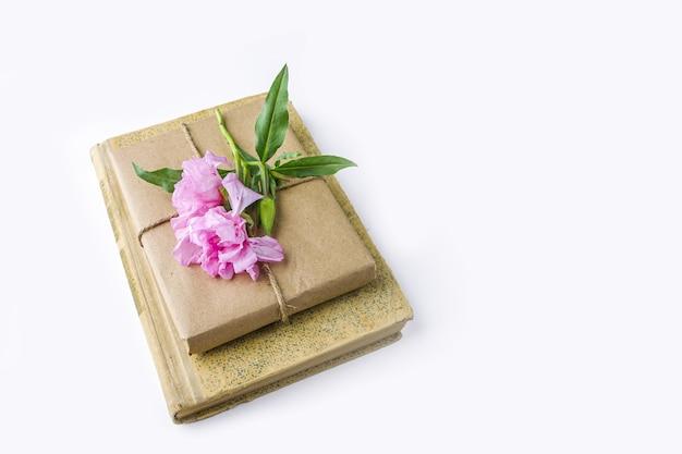 Romantyczna martwa natura w stylu vintage ze starą książką i ładnym pudełkiem owiniętym papierem rzemieślniczym i ozdobionym różowym kwiatkiem na białym tle