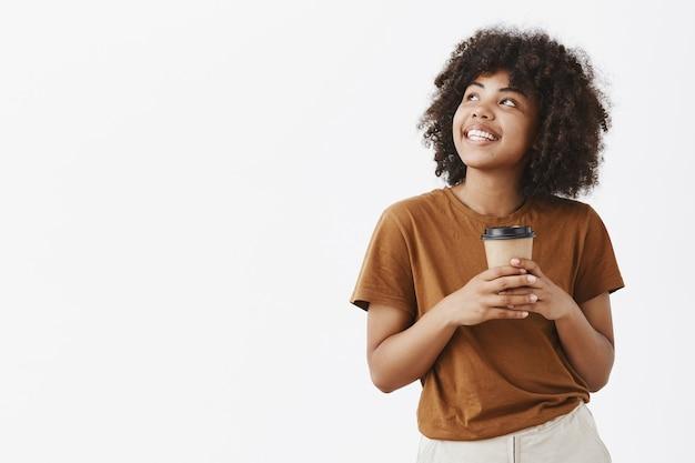Romantyczna marzycielska przystojna dziewczyna z fryzurą afro w brązowej koszulce trzymająca papierowy kubek z kawą i wpatrująca się z radosnym uśmiechem w lewy górny róg ciesząc się gorącym napojem i ładną pogodą