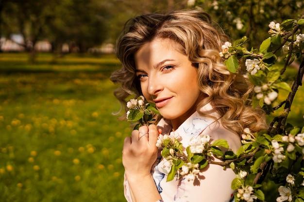Romantyczna młoda kobieta w ogrodzie wiosny wśród kwiat jabłoni. piękna kobieta, szczęśliwej wiosny