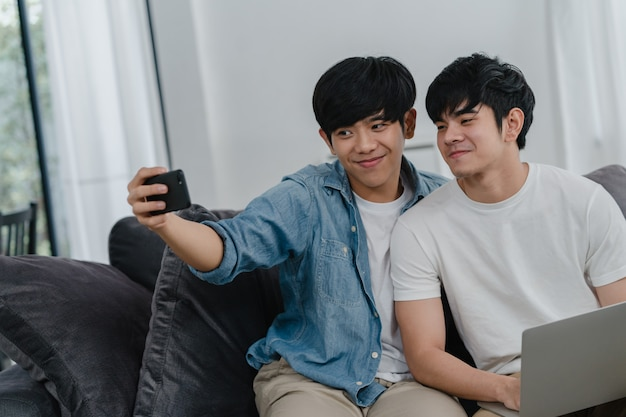 Romantyczna młoda para gejów śmieszne selfie przez telefon w domu. azjatyckiego kochanka męski szczęśliwy relaksuje zabawę używać technologia telefonu komórkowego ono uśmiecha się bierze fotografię wpólnie podczas gdy kłamający kanapę w żywym pokoju.