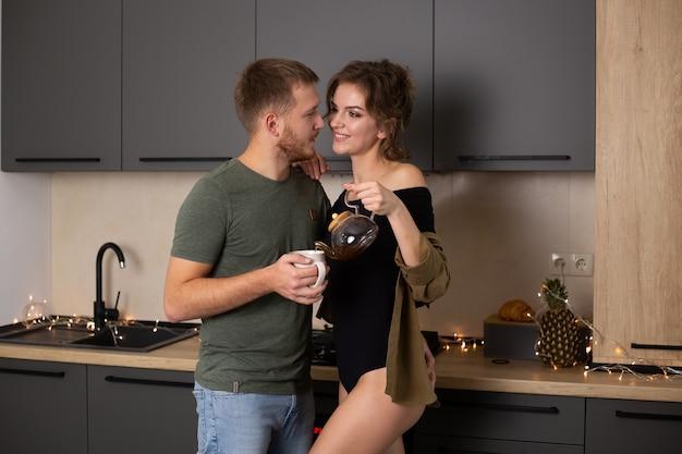 Romantyczna młoda para razem w kuchni, razem świetnie się bawiąc.
