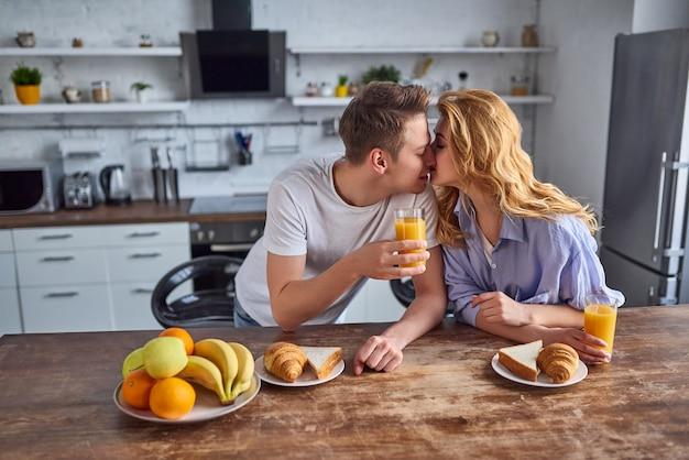 Romantyczna młoda para w kuchni. przystojny mężczyzna i atrakcyjna kobieta pić sok w kuchni i całować. zdrowy tryb życia.