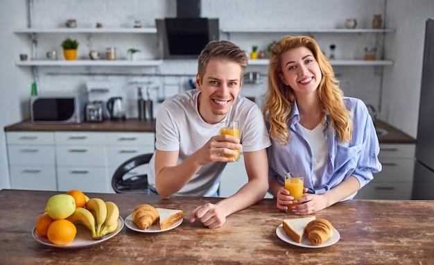 Romantyczna młoda para w kuchni. przystojny mężczyzna i atrakcyjna kobieta pić sok w kuchni. zdrowy tryb życia.