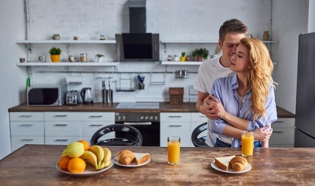 Romantyczna młoda para w kuchni. przystojny mężczyzna i atrakcyjna kobieta przytulanie w kuchni. zdrowy tryb życia.