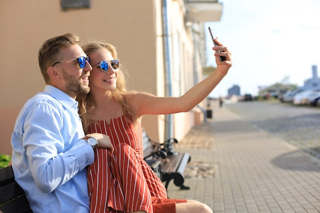 Romantyczna młoda para w letnie ubrania, uśmiechając się i biorąc selfie siedząc na ławce na ulicy miasta.