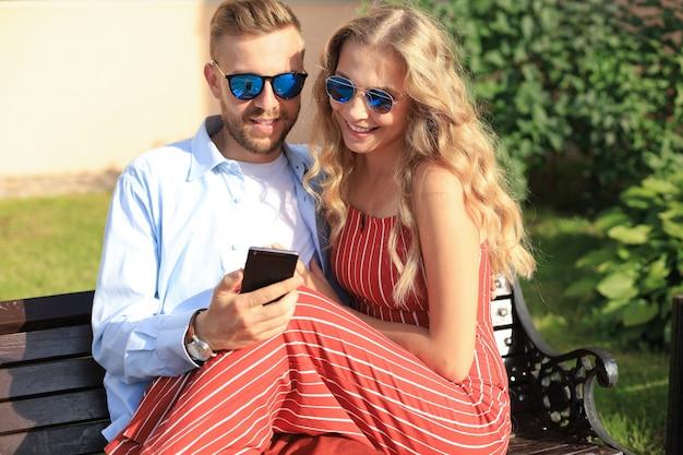 Romantyczna młoda para w letnie ubrania, uśmiechając się i za pomocą telefonu komórkowego, siedząc na ławce na ulicy miasta.