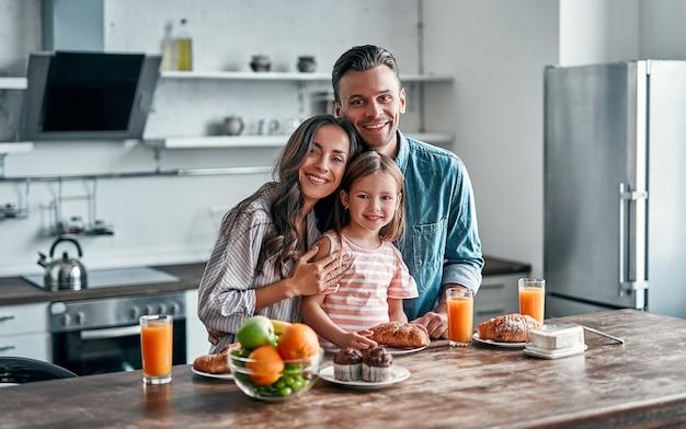 Romantyczna młoda para z córką w kuchni, przygotowując się do śniadania. szczęśliwa rodzina spędza razem czas stojąc na lekkiej, nowoczesnej kuchni.