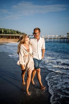Romantyczna młoda para zakochana razem na piasku spacery wzdłuż plaży morza śródziemnego. letnie wakacje w ciepłym kraju.