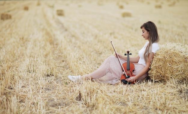 Romantyczna młoda skrzypaczka z rozpuszczonymi włosami i skrzypcami w dłoni siedzi na polu skoszonej pszenicy obok snopu siana