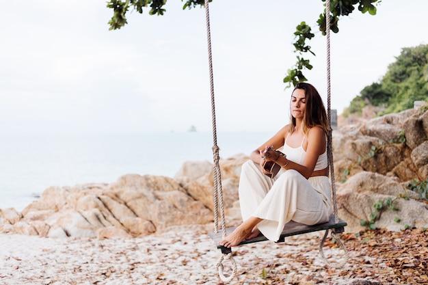 Romantyczna młoda szczęśliwa spokojna kaukaski kobieta z ukulele na tropikalnej kamienistej plaży o zachodzie słońca