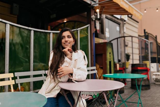 Romantyczna nieśmiała dziewczyna z długimi włosami, ubrana w biały płaszcz, siedząca w kawiarni francuskiej na zewnątrz i czekająca na randkę