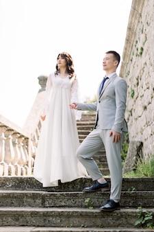 Romantyczna nowożeńcy para azjatyckich pozowanie w ruinach starego zamku, trzymając się za ręce i stojąc na kamiennych schodach