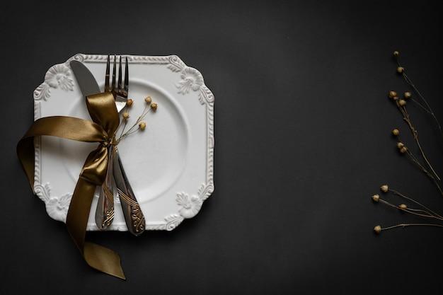 Romantyczna oprawa stołowa ze wstążką, talerzami, sztućcami na czarnym tle. pusty talerz. układ projektu makiety dla tekstu. miłość romantyczna koncepcja. skopiuj miejsce. widok z góry. leżał na płasko.