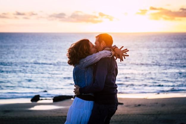 Romantyczna para ciesząca się zachodem słońca na plaży, całująca się i kochająca się nawzajem