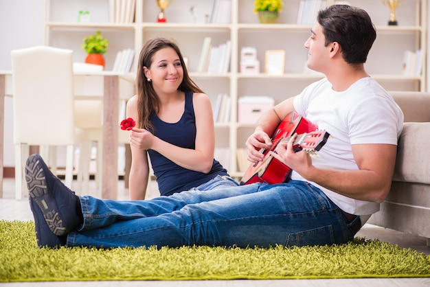 Romantyczna para gra na gitarze na podłodze