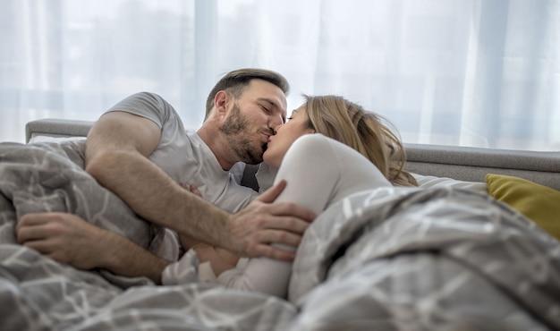 Romantyczna para leżąca w łóżku, obejmująca się i całująca?
