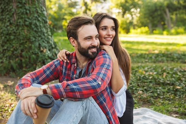 Romantyczna para mężczyzna i kobieta ubrani na co dzień, przytulająca się i pijąca kawę na wynos podczas odpoczynku w zielonym parku