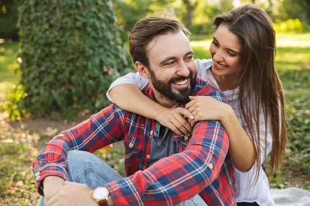Romantyczna para mężczyzna i kobieta ubrani na co dzień, przytulająca się podczas odpoczynku w zielonym parku