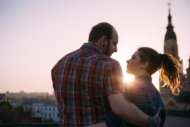 Romantyczna para na dachu w centrum uwagi na pierwszym planie. przytulanie ludzi razem ciesząc się zachodem słońca. wrażliwy wygląd, stylowe biodrówki, miejskie tło z wolną przestrzenią