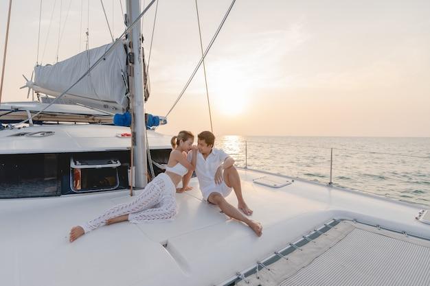 Romantyczna para na jachcie patrząc na piękny zachód słońca.