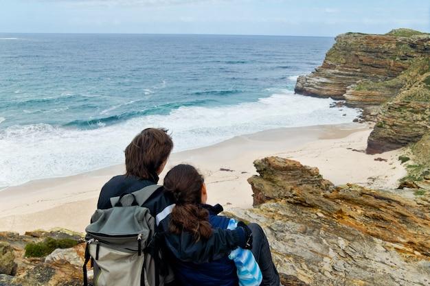 Romantyczna para patrząc na piękny widok na przylądek dobrej nadziei i ocean. wakacje poślubne w afryce południowej
