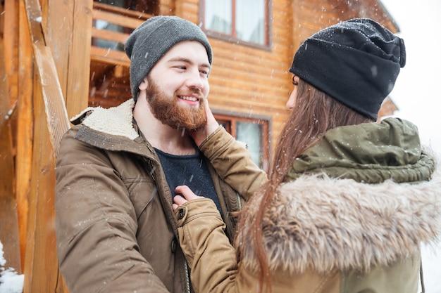 Romantyczna para przed drewnianą chatą