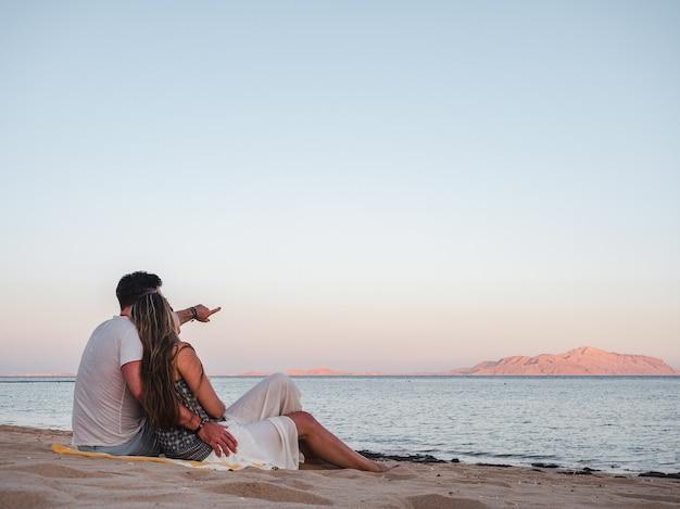 Romantyczna para siedzi na plaży i patrząc na morze