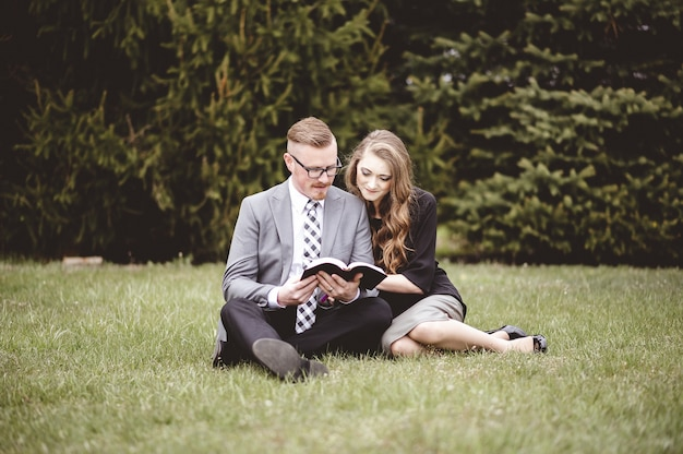 Romantyczna para siedzi na trawiastym trawniku i czule czytając książkę