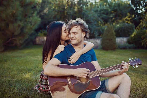 Romantyczna para siedzi na trawie w ogrodzie