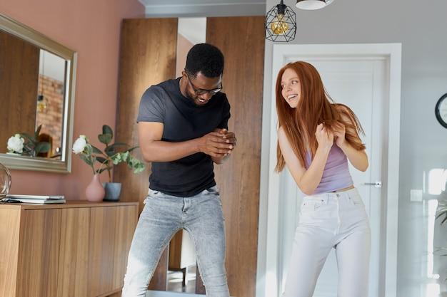 Romantyczna para śmieszne taniec w domu, atrakcyjny rudy i przystojny mężczyzna