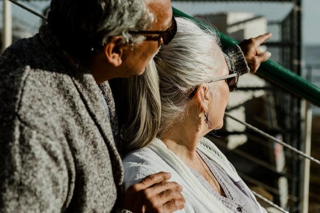 Romantyczna para starszych siedzących na molo