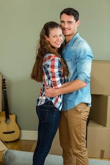 Romantyczna para stojąca twarzą w twarz i obejmująca się w nowym domu