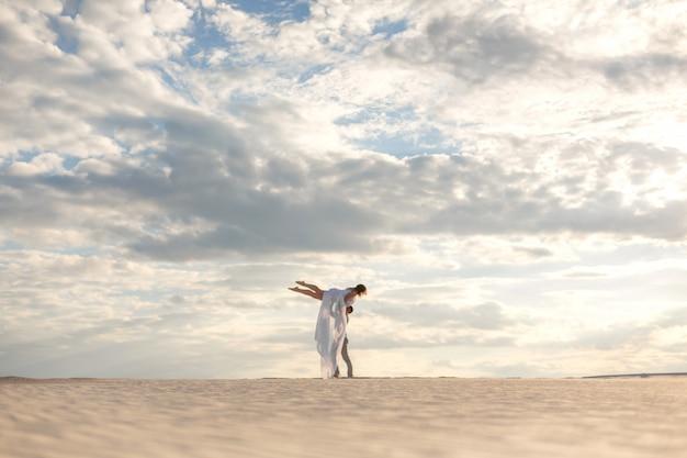 Romantyczna para tańczy w piasek pustyni. facet podnosi dziewczynę ponad siebie. niebo zachód słońca