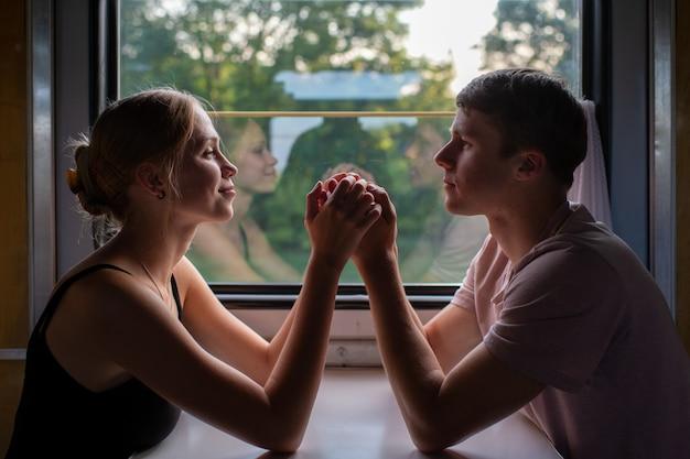 Romantyczna para trzymając się za ręce w pociągu.