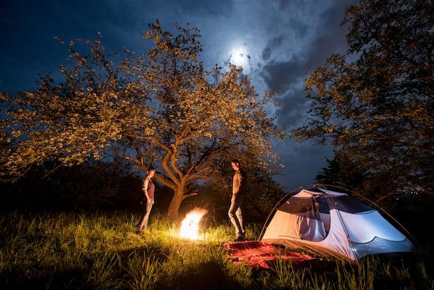 Romantyczna para turystów stojących przy ognisku w pobliżu namiotu pod drzewami i nocne niebo z księżycem. nocne biwakowanie
