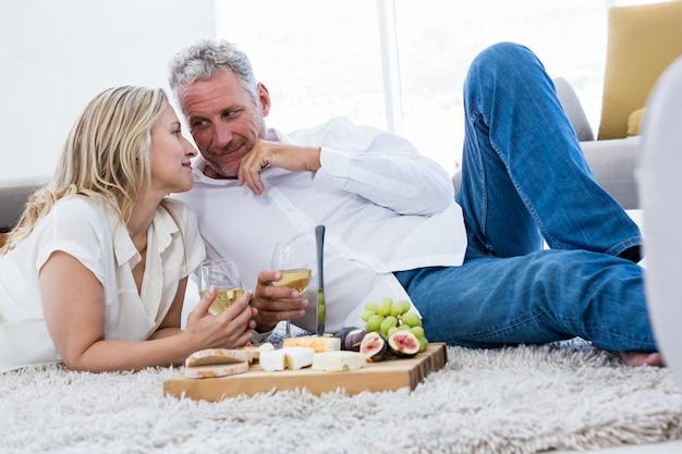 Romantyczna para z białego wina i jedzenia, leżąc na dywanie