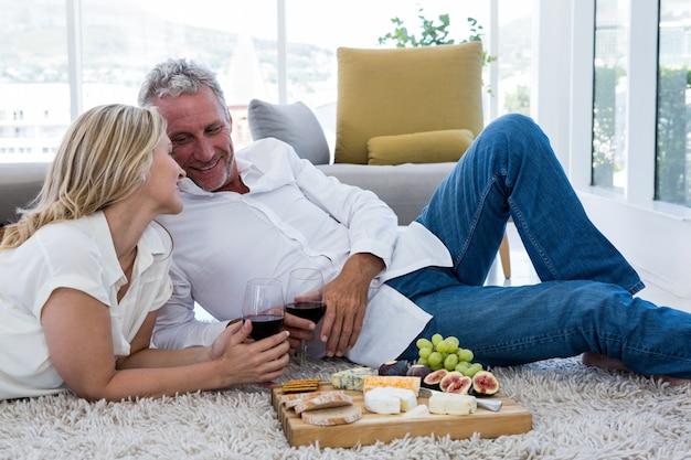 Romantyczna para z czerwonego wina i jedzenia, leżąc na dywanie
