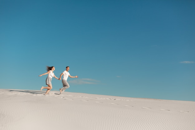 Romantyczna para zakochanych działa na białym piasku na pustyni.