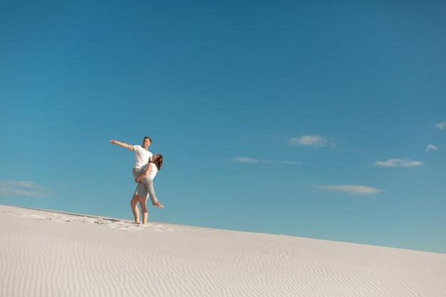 Romantyczna para zakochanych na białym piasku na pustyni. człowieku, trzymaj i wychowuj dziewczynę