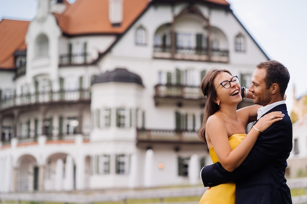 Romantyczna para zakochanych przytulanie przed starym budynku. młoda kobieta ubrana w żółtą suknię wieczorową, śmiejąc się radośnie po otrzymaniu dobrej nowiny. koncepcja szczęśliwych ludzi.