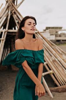 Romantyczna piękna kobieta ubrana w zieloną letnią sukienkę z odkrytymi ramionami z zamkniętymi oczami