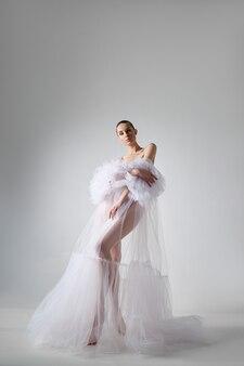 Romantyczna piękna kobieta w lekkiej sukience stoi na białym tle, długie nogi.