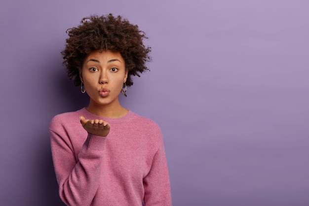 Romantyczna piękna kobieta z włosami afro wysyła zmysłowy pocałunek z otwartej dłoni