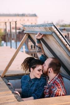Romantyczna randka na dachu. miłość para zbliżenie. scena filmowa, delikatne relacje. szczęśliwi i młodzi uśmiechnięci ludzie skupieni na pierwszym planie, w tle miejskim