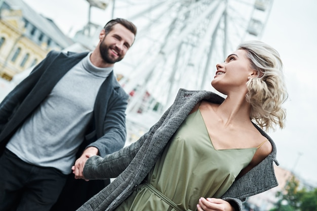 Romantyczna randka na świeżym powietrzu młoda para biega w parku rozrywki, trzymając się za ręce patrząc na siebie